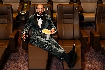 KLEIDER MACHEN LEUTE: With popcorn and tuxedo in the first row